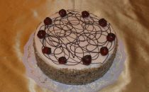 042 – Baileystorte, 20 cm Ø (10 – 12 kleine Stücke), dunkles Biskuit gefüllt mit Schokolade- und Kaffee-Baileyes-Creme. Mit Nüssen und Kirschen verziert.
